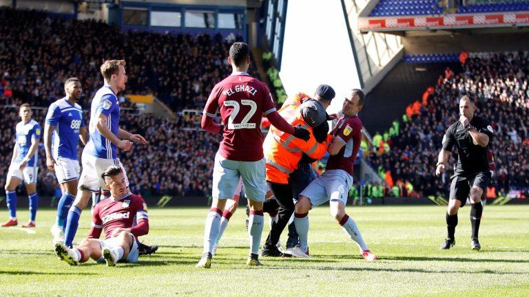 شاهد.. مشجع يعتدي على لاعب أثناء مباراة في الدوري الإنجليزي (فيديو وصور)